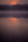 Sunrise in fog on Lake Cassidy with sun coming up behind trees Snohomish County Washington State USA