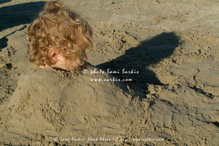 Little girl buried in sand at the beach, Prophete, Marseille, France.