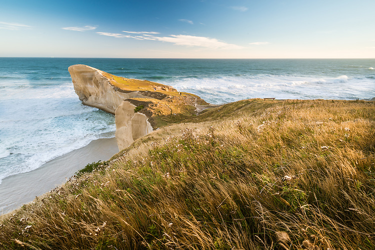 Warm evening light on the sandstone headland - Tunnel Beach Otago New Zealand - stock photo, canvas, fine art print