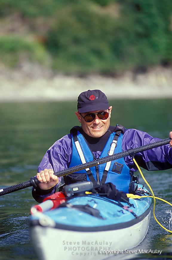 Senior man sea kayaking, San Juan Islands, WA.