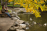 USA, Oregon, Ashland, a couple sit and watch the ducks swim in the Lithia River in Lithia Park