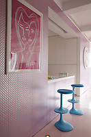 Metallic patterned wallpaper covers the wall between the living area and the kitchen with a pair of bright blue stools by the breakfast bar