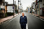 Tomioka, May 2 2012 - Naoto Matsumura, 52, refuses to leave the Fukushima nuclear evacuation zone. Since April 2011, he lives alone in his house without electrcicity and takes care of pets in the area. Mr Matsumura walking on the empty streets of Tomioka.