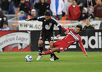 Chicago Fire midfielder Baggio Husidic (9) slides to defend the play against DC United forward Jaime Moreno (99) . The Chicago Fire defeated DC United 2-0 at RFK Stadium, Saturday April 17, 2010.