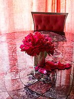 Close up of a bright red bunch of flowers on a glass table in the dining room