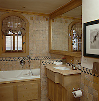 The bathrooms throughout the chalet are decorated in a combination of antique-look tiles and pine