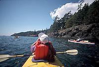 Woman kayaking around San Juan island, Puget Sound, Washington