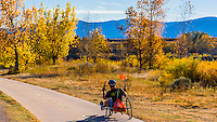 Man riding a low rider recumbent tricycle along the extensive bike trail system in Littleton, Colorado USA.
