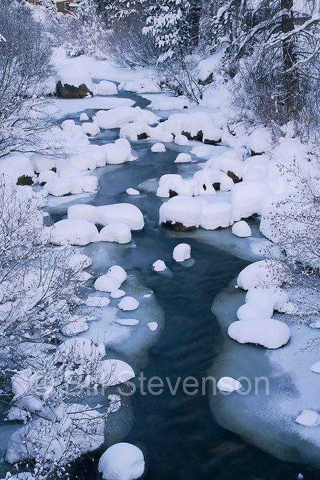 A photo of a mountain stream in winter with fresh new snow in the Sierras of California