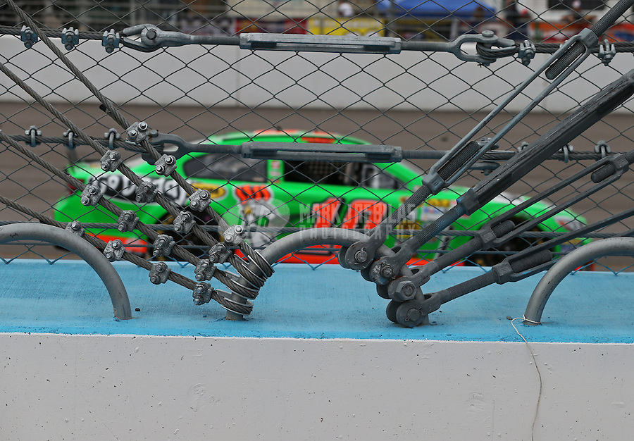 Mar. 3, 2013; Avondale, AZ, USA; Detailed view of the catch fence and cable containment system as NASCAR Sprint Cup Series driver Danica Patrick races by during the Subway Fresh Fit 500 at Phoenix International Raceway. Mandatory Credit: Mark J. Rebilas-