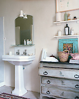 A distressed wooden chest of drawers and simple shelving provide storage in the bathroom