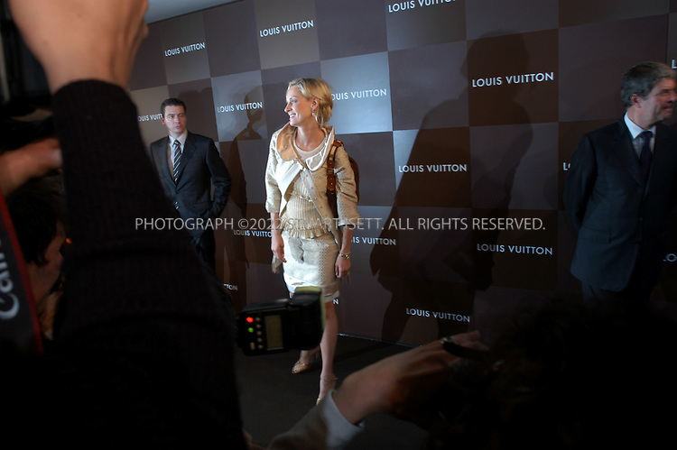 "10/9/2005--Paris, France..Actress Uma Thurman, with Louis Vuitton president Yves Carcelle right, arrives at the reopening party of the Louis Vuitton store and poses for paparazzi.  French luxury goods maker Louis Vuitton opened its biggest store yet on the Champs Elysees in Paris, after a 20-month redesign and enlargement project. The flagship store at 101, avenue des Champs Elysees has been redecorated and enlarged at an undisclosed cost...About 300 VIPs, including Hollywood stars Sharon Stone and Uma Thurman and French actress Catherine Deneuve, attended the official opening before American designer Marc Jacobs unveils his ready-to-wear spring-summer 2006 collection for Louis Vuitton. Behind the face-lift are US architects Eric Carlson and Peter Marino who sought to create a feeling of the famous promenade along the Champs Elysees continuing into the store...Throughout, it has features alluding to aspects of the fabled Champs Elysees such as brown and beige limestone flooring which echoes the paving stones on the street outside. Features include a light sculpture by American James Turrell, a 20-metre (65 feet) long ""travelling staircase"" showcasing the work of American video artist Tim White-Sobieski and an elevator linking the store to the top floor by Denmark's Olafur Eliasson..Photograph By Stuart Isett.All photographs ©2005 Stuart Isett.All rights reserved..Photograph By Stuart Isett.All photographs ©2005 Stuart Isett.All rights reserved."