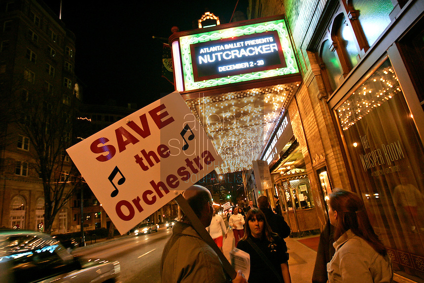 Tuba player Don Strand (holding sign) speaks with passersby in front of the Fox Theatre as members of the Atlanta Ballet Orchestra picket a performance of &quot;The Nutcracker.&quot; Last summer the Atlanta Ballet announced it would begin using recorded music for all of its productions and fired the orchestra. The American Federation of Musicians Local 148-462 has filed an unfair labor practice complaint. (Contact info: Mary Kenney of the orchestra (404) 888-0787)<br />