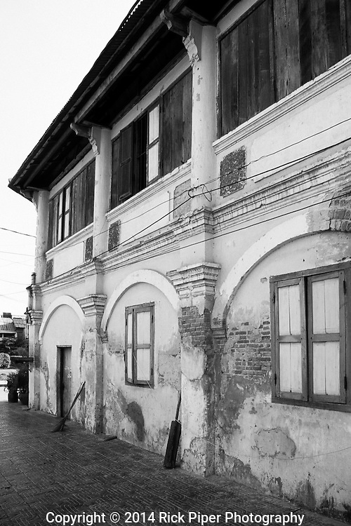 Weathered decaying old French colonial building in the centre of Kampot town, Cambodia.