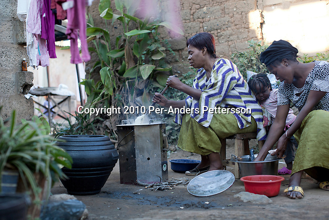 LUSAKA, ZAMBIA - JUNE 16:  Patricia Cheelo, age 52, uses a cook stove supplied by (CDM) Clean Development Mechanism on June 16, 2010, in Lusaka, Zambia. Patricia works at a school in Lusaka. She cooks with Flores Cheelo, age 21, one of her daughters. She cooks msima the staple food of this region and can be made from corn, cassava or other starch flour. CDM is one of the mechanisms in article 12 in the Kyoto Protocol that allows industrial nations to meet their CO2 emission reduction targets by investment and transfer of sustainable technologies in development countries. In Zambia, Lusaka Sustainable Energy project , is providing house-holds with cook stoves, financed by RWE Power AG, the German power utility. The project in Zambia seeks to switch charcoal consuming households to sustainable harvested sticks of wood used for the cookers, and by doing that saving trees and the environment in Zambia. House-holds are save a substantial amount of money every month by not buying charcoal, which usually is a major cost for poor people in the country. (Photo by Per-Anders Pettersson/Getty Images)