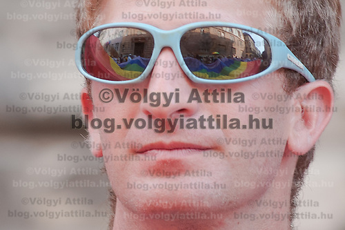 Rainbow flag of the Gay Pride March is reflected in the sunglasses of a participant in Budapest, Hungary on June 18, 2011. ATTILA VOLGYI