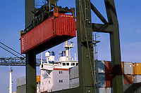 A cargo container being loaded onto a ship by crane.