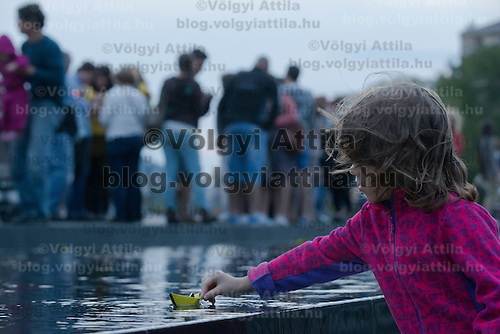 Child places a paper ship on the water to commemorate World Refugee Day at an event organised by Amnesty International in front of Hungarian Parliament in Budapest, Hungary on June 20, 2015. ATTILA VOLGYI
