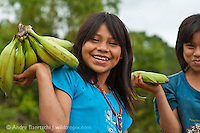 Machiguenga girls carrying bananas, Tayakome native communitiy, lowland tropical rainforest, Manu National Park, Madre de Dios, Peru.