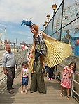 Brooklyn, New York, USA. 10th August 2013. Stilt walker KAE BURKE, of Lady Circus, holds a small young girl's hand as they pose for photo, during Burke's walk on the wood ramp leading to the famous boardwalk during the 3rd Annual Coney Island History Day celebration.