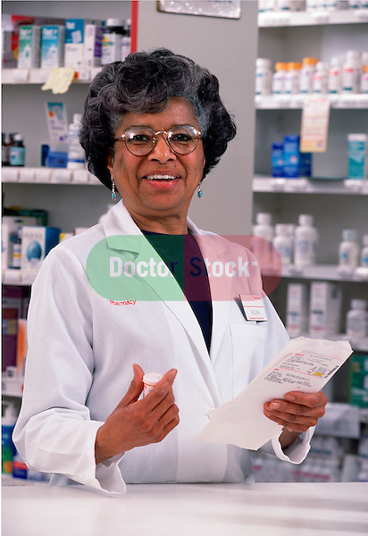 portrait of woman pharmacist at drugstore counter