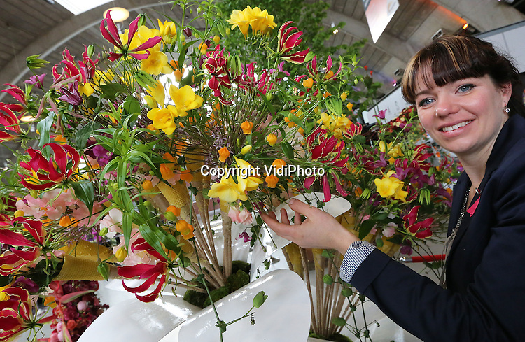 DEN BOSCH – Dini Holtrop (34) poseert donderdag bij haar winnende honingbijenboeket op de Floraliën in Den Bosch. De bloemiste uit Heerenveen mag zich vanaf donderdag Nederlands Kampioen Bloemsierkunst noemen. Ook de tweede plek ging naar een Friese deelneemster: Hanneke Frankema uit Sneek. Alex Aalders uit Assen veroverde de derde plek. Het NK Bloemierkunst wordt eenmaal in de vier jaar gehouden. Dini Holtrop mag nu ons land vertegenwoordigen op de Europese Kampioenschappen in Genua, Italië, medio september 2015. De Friese bloemiste won de prestigieuze finale van elf bloemisten en arrangeurs uit het hele land. De bloemwerken van alle deelnemers zijn nog tot en met zondag te zien op de Floraliën.
