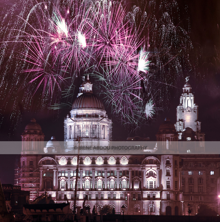 The fireworks display is viewed from Albert Dock during the August 29th, 2007 celebration of the 800th birthday of Liverpool, England's 5th largest city. A liver bird sits on the cupola of the clock tower at the right, marking the Royal Liver Building. On the left side of the building sits a second liver bird, looking in the opposite direction. According to legend, one liver bird gazes over the city in protection of its people, as the other guards the sailors coming home to port. The more modern local saying, though, is that one bird is waiting for the pubs to open, as the other looks out for handsome sailors...Liverpool, home of the Beatles and the Merseybeat poets, was once a proud hub of trade and culture until the 1970s, when its ports and manufacturing industries began a sharp decline. Now, years later, Liverpool is once again on the rise. Named as Europe's official Capital of Culture for 2008, Liverpool's cultural life is on display for the world to see...This photo is a composite of two images: from the standpoint of the photographer, the fireworks took place to the left of the building.  One photo of the fireworks and a high dynamic range composite photo of the building were merged in Adobe Photoshop CS2.