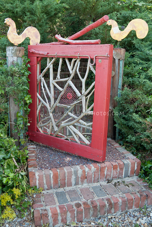 Garden gate entry, whimsical fun homemade artistic rustic branches in handmade fence gate with steps of brick, and bird ornaments roosters