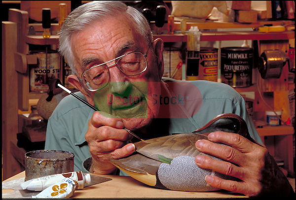 elder man painting a duck decoy