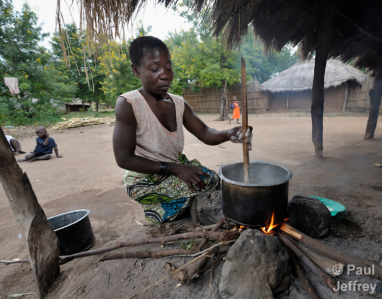 """Joyce Dzongololo cooks sorghum porridge for breakfast in Chidyamanga, a village in southern Malawi that has been hard hit by drought in recent years, leading to chronic food insecurity, especially during the """"hunger season,"""" when farmers are waiting for the harvest."""