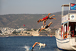 Local young men jumping into water with their dog from a boat in the harbor near Bodrum. Turkey