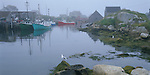 Halifax County, Nova Scota<br /> Fog on the harbor and boats at Peggy's Cove with exposed rocks at low tide