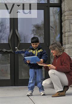 Asian boy ,age 6, with his adoptive Caucasian mother with books in front of the library, USA.