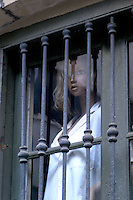 Mannequin in shirt looking out through bars of a window in Barcelona, Spain.