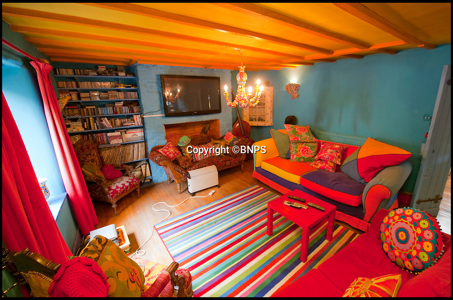 BNPS.co.uk (01202 558833)<br /> Pic: PhilYeomans/BNPS<br /> <br /> Lounge.<br /> <br /> Britain's wackiest property has come on the market...And the estate agents mantra of paint everything magnolia has definately not been applied.<br /> <br /> It may look like an idyllic cottage in the Forest of Dean from the outside but ceramic artist Mary Rose Young's unique taste has transformed the interior into what looks like something from Alice in Wonderland.<br /> <br /> The three-bedroomed house is decorated from head to toe in crazy colours, clashing patterns, and enormous murals,<br /> each room is covered in the garish designs, including the bathroom, where even the sink and toilet have been adorned in bright tiles.<br /> <br /> Estate agents Bidmead Cook now have the tricky task of showing prospective punters round the £500,000 property.