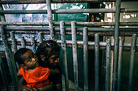 A girl babysits her younger brother near their house in one of the Ebeye's slums.