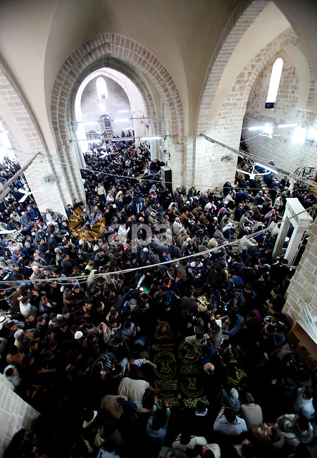 Palestinians pray near the bodies of Islamic Jihad militants during their funeral in Gaza March 10, 2012. Israel killed two more Gaza militants on Saturday, raising the death toll in two days of violence to 12 and dozens of rockets fired from Gaza into Israel injured at least four people, Israeli and Palestinian officials said.  Photo by Ashraf Amra