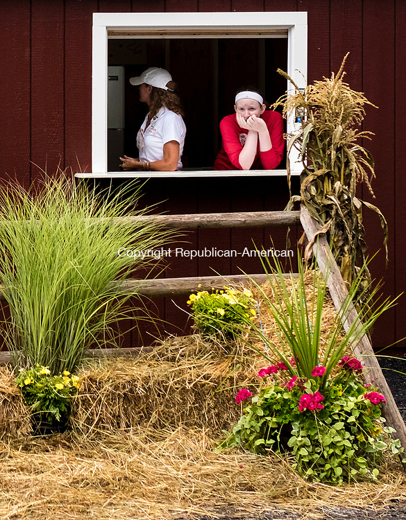 Wolcott, CT-18 August 2017-081817CM01-  Michelle Reignier, left, and her daughter Lou Lou Barnes, both of Wolcott wait for customers at a food booth during the Wolcott Country Fair on Friday.  The fair continues Saturday and Sunday with gates opening at 10 a.m. and closing at 10 p.m.      Christopher Massa Republican-American