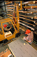 Sheet Metal Warehouse, two men in hardhats, one driving a forkloader, one with paperwork. occupations, building, construction materials,.