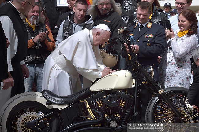 Pope Francis signs a Harley Davidson motorbike of the Christian motorcycle group ''Jesus Bike''  of Wurzburg during the weekly general audience at the Vatican, May 29, 2019.