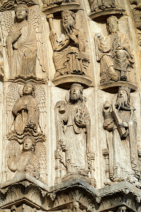 West Facade, Central Portal, Archivolts- Right c. 1145. Cathedral of Chartres, France . Gothic statues of figures, from  the center the inner archivolt contains figures of angels standing on clouds. They hold round objects. (Perhaps these are wheels- the symbol for the Thrones, one of the choirs of angels described in Old Testament Book of Ezekiel 1:13-19. - JV) .The outer archivolts (right) contain figures of the Elders of the Apocalypse (Apocalypse, Chapter 4). They are depicted as bearded, haloed men wearing crowns seated on thrones. Each holds a musical instrument (Apocalypse, 5:8). A UNESCO World Heritage Site.