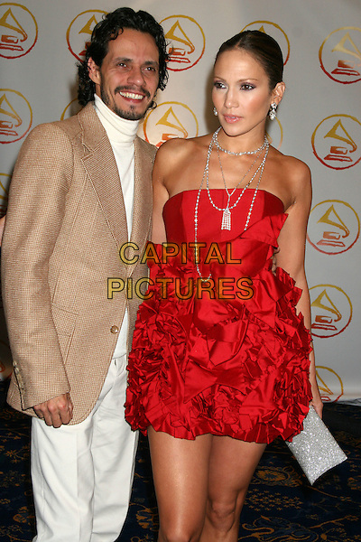 MARC ANTHONY & JENNIFER LOPEZ.The 2006 Latin Recording Academy Person Of The Year Tribute honoring Ricky Martin at Sheraton Hotels & Towers, New York, USA..November 1st, 2006.Ref: IW.half length married husband wife white trousers beige suit jacket red strapless dress gathered ruffles silver clutch purse.www.capitalpictures.com.sales@capitalpictures.com.©Ian Wilson/Capital Pictures