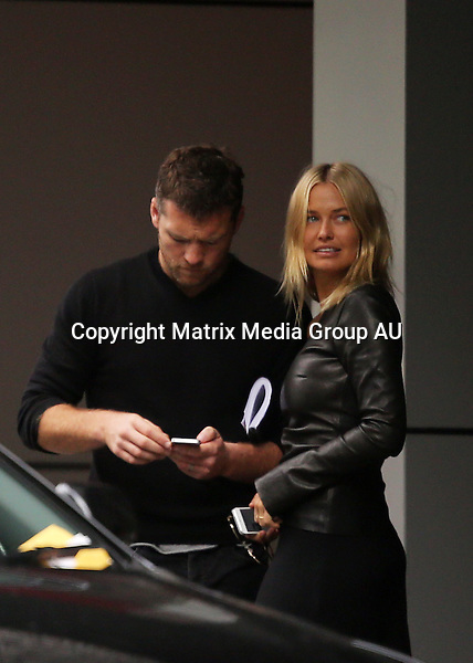 23 JANUARY 2014 SYDNEY AUSTRALIA<br /> <br /> EXCLUSIVE PICTURES<br /> <br /> Lara Bingle pictured with Sam Worthington at a bank in Surry Hills. After a meeting with the manager Lara and Sam took off in different directions - Sam took a ride in an Uber limo while Lara joined her friend Vicki Lee to pick up some supplies from an art supplies shop in Bondi. While she waited Lara made friends with a cute little dog.