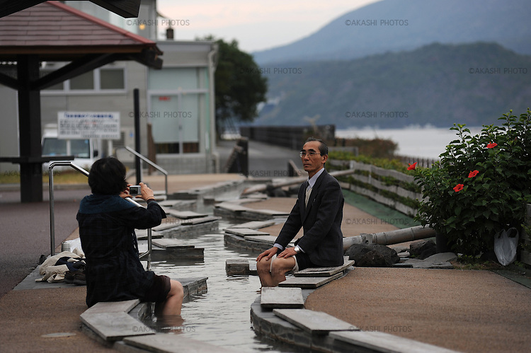 A Japanese couple taking pictures of themselves with Sakurajima behind while they put their feet on Ashi Yu, hot spring for feet.