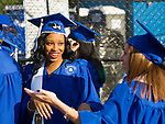 WATERBURY, CT-062117JS05- Crosby graduates Destiny Hines, left, and Megan Holland, right, share a light-hearted moment as they make their way onto the football field for graduation ceremonies Wednesday.  Jim Shannon Republican-American