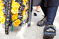 "Melvin Bodenheimer aka ""Little Dempsey"" shows off his unique footwear at a parade held in Buddy D's honor on January 31, 2010 in New Orleans.<br /> <br /> Thousands of Saints fans wearing dresses paraded from the Louisiana Superdome to the French Quarter to honor a promise made by the late sportscaster and Saints super-fan Buddy Diliberto aka ""Buddy D"".<br /> <br /> In 1993 Buddy D, who passed away in 2005, remarked on air that if the Saints were to make it to the Super Bowl, he would wear a dress and dance down the streets.  The comment was repeated at various times and never forgotten by his listeners.<br /> <br /> Led by former New Orleans Saints quarterback Bobby Hebert, who has taken Buddy D's place on WWL radio, thousands made good on his promise for him, dancing, drinking, and cavorting their way down the street, alternately yelling out ""Who Dat!"" and ""Buddy D!"" in front of an onlooking crowd an estimated 85,000 people strong.<br /> <br /> The hard luck NFL team the New Orleans Saints has reached its first Super Bowl in team history, after 43 years largely filled with losing seasons and futility.  It is difficult to travel anywhere in the area without some reminder of this fact, as the team and city are intertwined perhaps like no other sports franchise in this country."