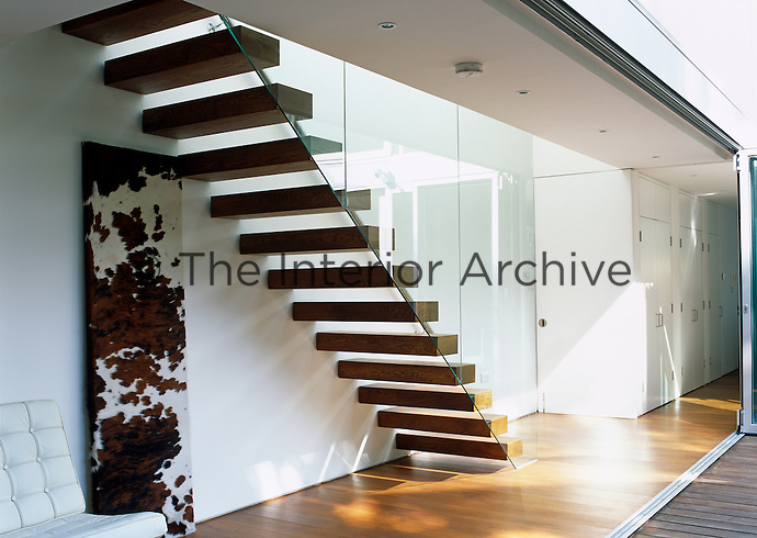 A wooden cantilevered staircase encased in a glass wall leads up to the first floor