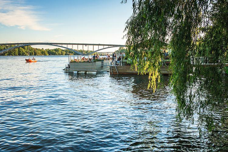 Liten segelbåt far förbi restaurant vid Riddarfjärden på Kungsholmen i Stockholm