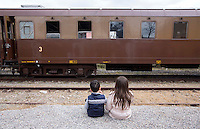 Due bambini seduti sul marciapiede della stazione di Torrenieri-Montalcino, davanti a un treno d'epoca degli anni Venti, in occasione della presentazione degli itinerari storici proposti dal Ministero dei Beni Culturali e del Turismo e dalla Fondazione FS Italiane, lungo il tracciato dell'antica ferrovia della Val d'Orcia, 11 aprile 2015.<br /> Two children sit in front of a vintage train of the twenties traveling on the occasion of the presentation of the historical tours proposed by the Italian Culture and Tourism Minister and Fondazione FS Italiane (Italian Railways Foundation), at Torrenieri-Montalcino's railway station, along the Val d'Orcia, Tuscany, 11 April 2015.<br /> UPDATE IMAGES PRESS/Riccardo De Luca