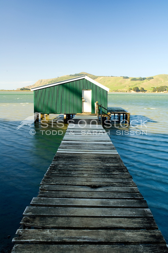 Wooden boardwalk and green corregated iron boatshed on the Otago Peninsula, South Island, New Zealand - stock photo, canvas, fine art print